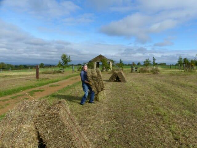 Volunteer shifting Hay Bales at Sun Rising Natural Burial Ground and Nature Reserve