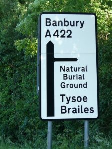 Sign on A422 travelling from Stratford-upon-Avon to Banbury, pointing right to Sun Rising Natural Burial Ground.
